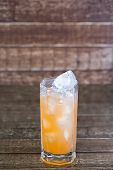 Juice drinks grapefruit with the broken ice on a wooden background