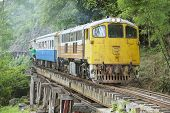 Vintage locomotive passes Death railway in Kanchanaburi, Thailand.