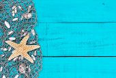 Starfish and shells in fish netting on teal blue wood beach sign