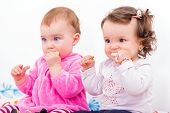 picture of teething baby  - Photo of two adorable baby sitting on the bed and nibbles