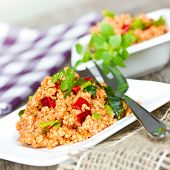 stock photo of tabouleh  - couscous with paprika on white plate close up  - JPG