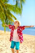 Young Fashionable Boy Enjoys Life On Tropical Beach