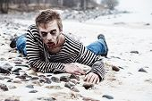 stock photo of insane  - Insane man crawling weakly on the seaside - JPG