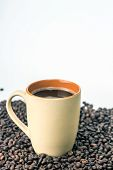 Coffee cup and saucer on table of coffee beans. White background