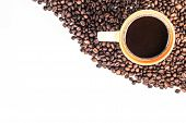 orange cup of coffee on beans with copy space. top view