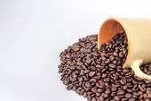 ceramic orange mug on a pile of roasted coffee beans