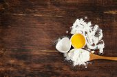 wooden baking background with raw eggs and flour