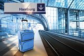 Departure For Hamburg, Germany. Blue Suitcase At The Railway Station