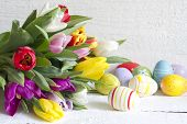 Easter eggs and tulips on wooden board