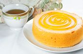 foto of sponge-cake  - Sponge orange cake dessert with tea cup on table - JPG