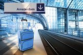 Departure For Amsterdam, Netherlands. Blue Suitcase At The Railway Station
