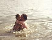 toned portrait of Father and Daughter Playing Together at lake