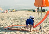 Sweet Toddler Dressed As A Sailor Climbing On A Sunbed With View From His Back. Photo With Untraditi