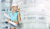 Woman in hard hat holding drawing rolls, talking on walkie talkie
