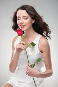 Woman with perfect skin, long hair and rose