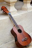 picture of ukulele  - ukulele brown for playing music put on the floor - JPG