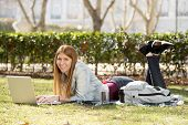 Young Student Girl Lying On Park Grass With Computer Studying Or Surfing On Internet