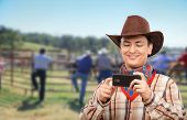 foto of cowboy  - Cheerful cowboy is surfing the internet on a smartphone - JPG