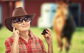 picture of cowgirl  - Aged cowgirl is listening music on her smart phone - JPG