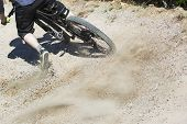 pic of gravity  - Unfiltered version of mountain bike rider drifting through a gravity of an artificial downhill track - JPG