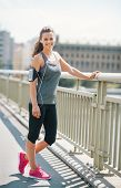 stock photo of beats  - An athletic woman in pink sneakers stands on bridge smiling and resting - JPG