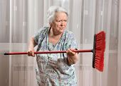 picture of broom  - Old angry woman threatening with a broom at home - JPG