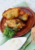 foto of tartar  - Delicious Breaded Fish Cutlets with Garlic Greens and Tartar Sauce on Brown Plate with Wooden Fork closeup on Green Napkin - JPG