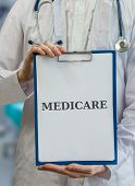 stock photo of infirmary  - Doctor holds blue clipboard with medicare written - JPG