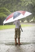 picture of wet pants  - a young bare foot person standing and holding a red white and blue umbrella during a deluge of rain - JPG