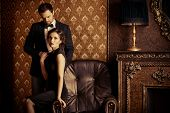 Beautiful man and woman in elegant evening clothes in classic vintage apartments. Glamour, fashion.  poster