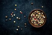 image of peppercorns  - Peppercorns in a wooden bowl on a dark background - JPG