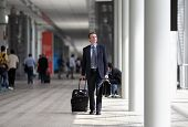 stock photo of trolley  - businessman walking with trolley through the crowd on a business travel - JPG