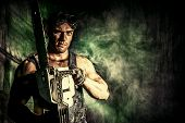 stock photo of chainsaw  - Handsome muscular man with a chainsaw over dark grunge background - JPG