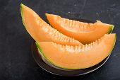 stock photo of cantaloupe  - Fresh cantaloupe melon slices on a dark background - JPG