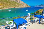 pic of greek-island  - Blue wooden tables and chairs with view on sea bay on Greek Island - JPG