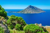 foto of greek-island  - Amazing view on Greek volcano Island with green bushes in foreground - JPG