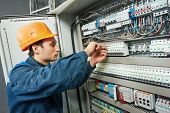 picture of fuse-box  - electrician with screwdriver tighten up switching electric actuator equipment in fuse box - JPG