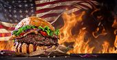 foto of hamburger-steak  - Delicious hamburger with fire flames and american flag on wooden background - JPG
