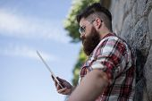 image of moustache  - Handsome big moustache hipster man in the city with tablet - JPG