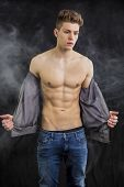 picture of undressing  - Attractive trendy athletic fit young man undressing, taking off t-shirt, on dark smoky background