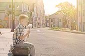 stock photo of dandelion seed  - 4 years old little kid sitting on pavement on old vintage suitcase and blowing dandelion seeds in sunny summer morning on deserted street - JPG