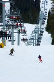 Very busy snow ski resort with four person chair lift