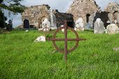 ancient monument and burial concept - old rusty grave cross, headstones and ruins on celtic cemetery poster