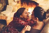Mom with child playing and chilling by the fire place some cold evening, winter weekends, cozy scene poster