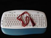 stock photo of tasbih  - a rosary or praying beeds on the key board of a computer  - JPG