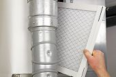 stock photo of furnace  - Male arm and hand replacing disposable air filter in residential air furnace - JPG