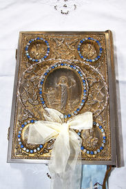 pic of ecclesiastical clothing  - the ecclesiastikal book with the wedding rings on the table with white linen - JPG