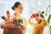 Family shopping. Mother and her daughter are holding grocery shopping bag with vegetables. poster