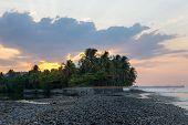 Beach At Sunrise With Dark Rocks And Nice Sunrays poster