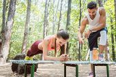 Beautiful woman doing a plank with man watching and cheering poster
